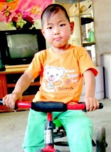 PD1: Jory appears young in this photo, where he is riding a tricycle, wearing an orange t-shirt & green pants in his foster home. He has a calm expression, black hair, and dark brown eyes.