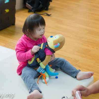PD:  Anabelle sits on a mat on the floor, holding a toy monkey in her lap & looking at it intently. She wears a pink hooded sweatshirt & blue jeans. She has pretty, dark hair that frames her face, along w/ bangs/fringe, & beautiful almond-shaped dark brown eyes.