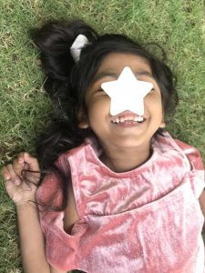 PD: *Blaire lays on her back in the green grass, wearing a baby pink velvet dress! She has light brown skin, her long, shiny black hair is pulled into a high pony w/ a silver scrunchie, & her brilliant smile is visible under the graphic that covers part of her face to protect her identity!