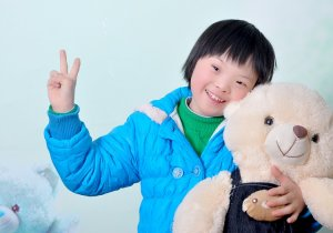Chessa is hugging a huge teddy bear in her photo! She's wearing a blue winter coat w/ a green sweater underneath & is showing a peace sign to the camera w/ her free hand. She has short black hair & dark eyes, along w/ a charming smile!