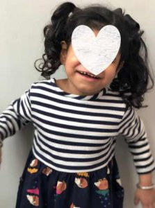 PD: *Eden has curly black hair in 2 high pigtails w/ black bow; she smiles shyly & has a graphic over part of her face to protect her identity. She wears a black/white striped dress w/ black patterned skirt & bangles.