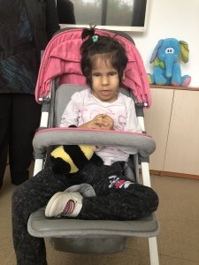 PD: Harmony sits in a stroller w/ hands clasped, & a soft toy on her lap, wearing a white long-sleeve t-shirt, black pants, & white clogs. She has an olive complexion & short, dark hair pulled into a ponytail on top of her head.