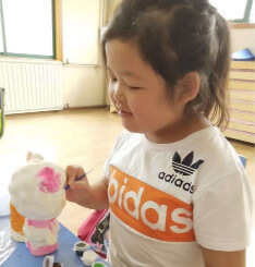 PD: Hedda is doing a craft in a classroom. She wears a white & orange Adidas t-shirt. She appears to be concentrating intently on painting a figure, & has a slight smile. Her black hair is pulled up into a ponytail.