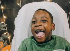 PD: Jonah sits in his positioning chair, which is covered w/ a blanket, wearing a green sweater & a gigantic smile! Jonah appears to be of African descent, & has a beautiful medium to deep complexion, deep, expressive brown eyes, & black hair cropped short.