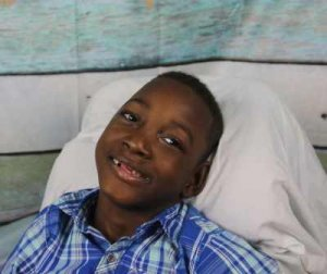 PD: Jonah sits in his blanket-covered chair, wearing a blue plaid button-down. He has a big smile & is missing most of his front teeth! The wood plank wall behind him is painted blue, white, & green.m