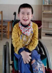 PD: Joshua sits in his wheelchair in a school setting, wearing a yellow long-sleeve shirt & jeans w/ a bandanna around his neck & a brilliant smile! He has short, black hair & almond-shaped brown eyes.