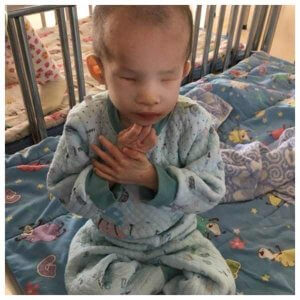 PD: Kassidy sits in a crib w/ her legs criss-cross applesauce, clutching her hands near her face. She is not smiling & appears very thin & sickly. She wears a blue patterned sweatsuit.