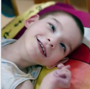 PD: Kaysen lays on a colourful blanket. This photo is a close-up of his face. His hair is shaved short & he has big, brown eyes. His tiny hand is curled up next to his face & despite his situation, he is smiling.