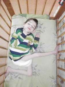 PD: Kaysen lays in a wooden crib, wearing only a diaper & striped shirt. His little body is twisted so 1 leg is bent at 90 degrees under him, the other straight out in front of him as if in a sitting position; his torso is turned facing up. His tiny hands are up around his face & he looks absolutely lifeless.