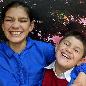 PD: Kelsi & Kameron are embracing, w/ huge, squinty smiles on each of their faces! Kelsi wears a blue windbreaker & Kameron a red sweater w/ white collared shirt underneath. Both have medium-light complexions and dark hair.