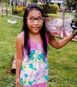 PD: Kristal wears a floral tank top, standing outside in what appears to be a park. She has long, black hair parted on the side & wears square-rimmed glasses.