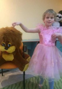 PD1: An updated photo of Leena! She has light blond hair & is wearing a pink frilly princess dress, standing next to a huge stuffed animal almost the size she is! She has 1 hand hovering above the toy, & the other held near her chest.