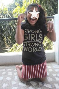 PD: *Lily tall-kneels on the balcony, wearing a red & burgundy striped skirt & black t-shirt w/ gold writing that says: 'strong girls, strong world'! Her hands are up triumphantly in 2 fists, w/ gold bangles on each arm. She has a half-up side ponytail &  a huge, open-mouthed grin! Part of her face is covered to protect her identity.