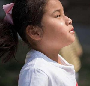PD1: *Lizzie wears a white t-shirt w/ pink bow in her ponytail. Her face is uplifted & the sun shines down on her.