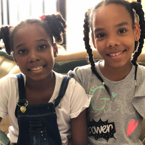 PD: Luna (l) and Lizzie (r) sit next to each other, smiling, illuminated by the window behind them. Luna wears a white t-shirt w/ overalls & her hair in 2 curly pigtails w/ pink bows. Lizzie wears a gray t-shirt that says 'girl power' w/ her long hair in 2 high braids. Luna has a deep complexion, whereas Lizzie's is a medium tone; both have beautiful brown hair & eyes.