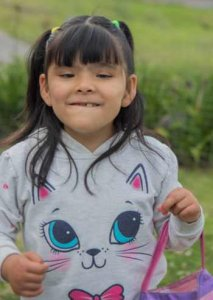 PD1: Lucia stands outside in front of some greenery, wearing a gray kitty-cat face-printed sweatshirt w/  a pink & purple purse over one arm. Her dark brown hair is in 2 half-up pigtails & she has bangs. She has a medium complexion & dark brown eyes.
