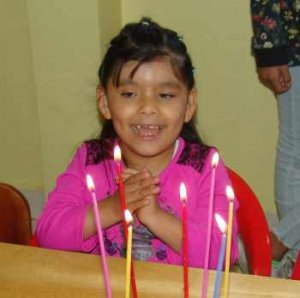 PD2: Lucia sits in a chair at a table w/ presumably a cake in front of her (only 7 tall, colourful candles are visible). She wears a pink jacket & her hair is in a half-up ponytail. She is smiling broadly, showing her dimples & missing front tooth! She has her hands clasped in front of her.