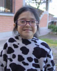 PD2: Marisol is standing outside, wearing a cow-print sweater & purple square eyeglasses. Her hair is longer than the previous photo, pulled back into a ponytail. She looks older & has a sweet smile on her face, making eye contact w/ the camera.