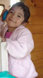 PD1: Marisol holds a toy phone up to her ear, leaning on some other play equipment in a pink t-shirt & sweater. She has a sweet, closed-mouth smile, dark brown eyes, light to medium skin tone, & dark hair.