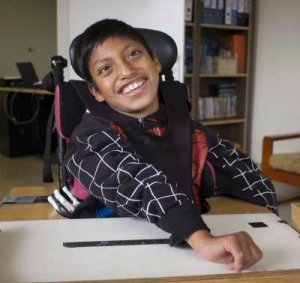 PD2: Mateo sits at his desk in his wheelchair, his arm stretched across the table in front of him. He has a huge, brilliant smile, making direct eye contact w/ the camera wearing a black sweatshirt w/ large white pinstripe checks.