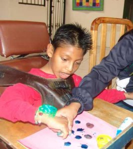 PD1: Mateo is working hand-over-hand w/ an adult to make dotted art on a piece of pink paper. He sits in a special chair pushed up to a desk w/ chest support. Mateo looks to be concentrating hard! He has dark brown eyes, medium skin, & dark hair spiked w/ gel! He wears a red sweatshirt w/ some bracelets on 1 wrist.