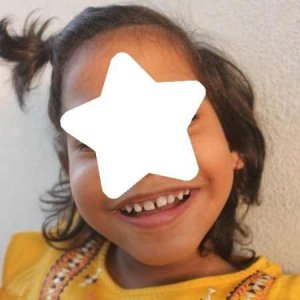 PD: *Mikayla's short, medium-brown hair is pulled half-up into a pigtail & she has a large, gap-toothed smile! She wears a yellow dress w/ multi-colored trim on the shoulders. She has a star graphic over her face to protect her identity.