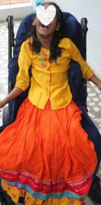 PD2: *Molly on her 12th birthday, wearing a beautiful gold & neon orange traditional Indian top & skirt w/ contrasting blue headband, sitting in her wheelchair w/ a huge grin!
