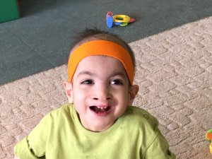 PD: Molly May has a big, open-mouthed smile! She's standing on a gray carpet, wearing a neon green shirt & orange headband. She has big, dark brown eyes & dark brown hair.