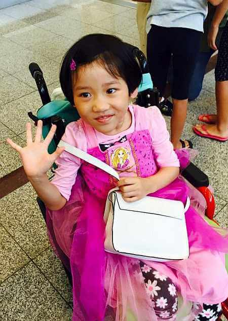 PD: Patti sits in her wheelchair, wearing a pink Rapunzel princess dress over a pink t-shirt & flowered pants. She smiles slightly, holding a purse around her w/ 1 hand & waving w/ the other. She has a pink clip in her short hair & a slight smile.