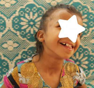 PD: In a recently-updated photo, *Penny sits in front of a teal & white paisley wall w/ her dark brown hair pulled back & a goofy smile w/ her tongue poking out. She also has a star over her eyes to protect her identity. She wears a multi-coloured top w/ gold circles in doily shapes at the neckline.