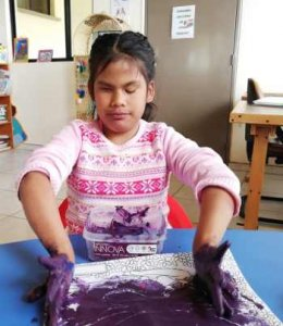 PD2: Rebekah sits at a table, finger-painting w/ purple paint. Her hair is in 2 pigtails down her back & she wears a pink snowflake-print alpine sweater w/ a  neutral expression.
