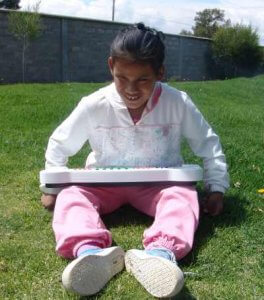 PD1: Rebekah sits on the grass outside w/ a toy musical keyboard in her lap, wearing a white sweatshirt & pink sweatpants. She has dark hair in a ponytail & medium skin, & a shy smile is visible on her face.