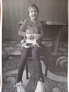 PD1: In this black & white photo, Hannah sits in a chair in a patterned, carpeted room w/ a desk behind her, wearing a long-sleeved t-shirt, leggings, & tennis shoes. She is smiling shyly, holding something between her hands. It appears she may have some strabismus (eyes that cross). How I wish this photo was in colour!