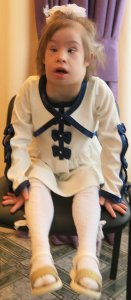 PD1: Tiny Paige sits in a chair, wearing a white dress w/ black trim, white tights, & sandals, w/ a huge white bow in her long blonde hair. She looks so much healthier than previous photos.