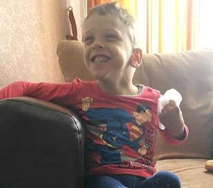 PD: Tiny Preston sits on a big brown sofa w/ 1 arm over the side, wearing a red Superman shirt & holding something in his opposite hand. He has a huge smile that squints his eyes!