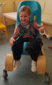 PD: Anders sits in a blue adaptive wheelchair supported by a chest harness, holding a Sophie the giraffe toy in 1 hand. He has a brilliant smile & bright blonde hair. His smile is so big, I can't tell what colour his eyes are! He wears a gray & orange long-sleeved shirt, black pants, & white shoes.