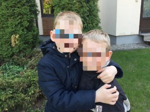 PD: Iggy & Aggy stand outside in front of greenery w/ their arms around each other. Both have white-blond hair & their faces are blurred to protect their identity due to country requirements. Both boys wear matching navy blue jackets.