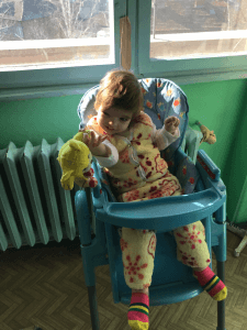 PD2: Sally sits in a high chair in front of some windows, focusing on a stuffed toy which she is holding in her right hand, wearing the same yellow suit as previous.