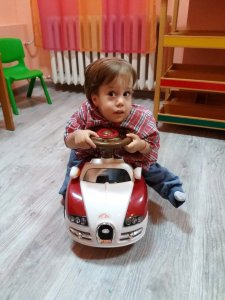 PD: Myrtie sits on a ride-on car toy, wearing a red checked shirt & blue jeans. He has a curious expression, brown eyes, & short brown hair.