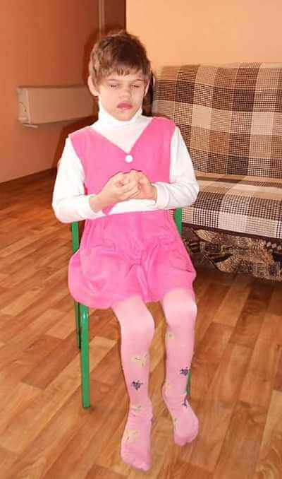 PD: Wendy sits in a chair, twisting her hands together. She wears a pink dress & pink tights w/ a white turtleneck underneath.